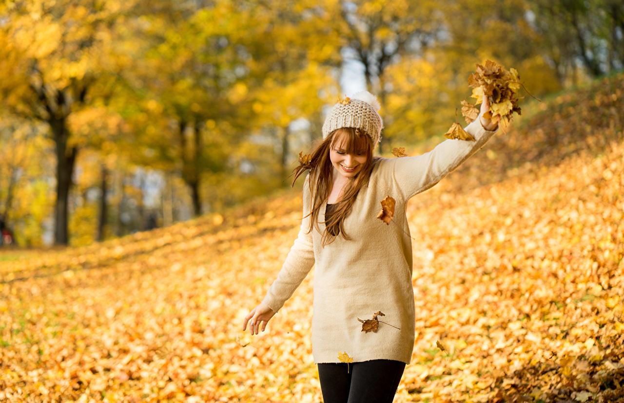 Фотография Листья Улыбка боке Осень Шапки Девушки Природа свитера лист Листва улыбается Размытый фон шапка в шапке осенние девушка молодая женщина молодые женщины Свитер свитере