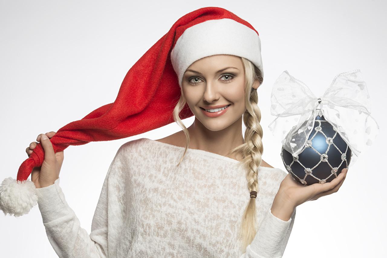 Обои Блондинка Рождество Коса Улыбка Шапки Девушки Шар Руки Бантик Серый фон Новый год косички Шарики