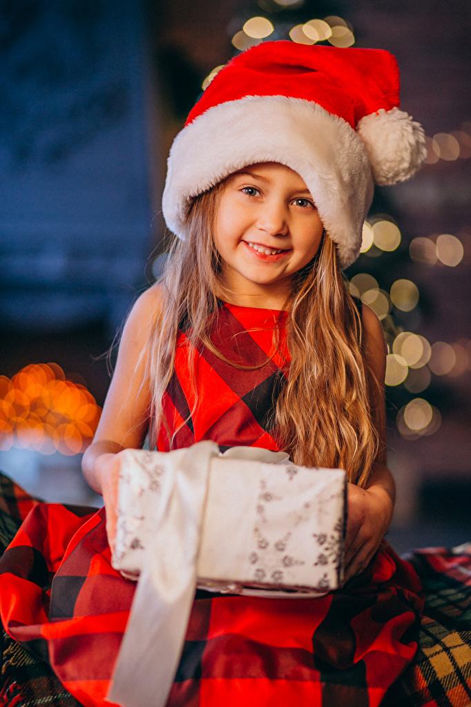 Обои для рабочего стола девочка Рождество Улыбка ребёнок Шапки подарок Взгляд  для мобильного телефона Девочки Новый год улыбается Дети шапка в шапке Подарки подарков смотрит смотрят