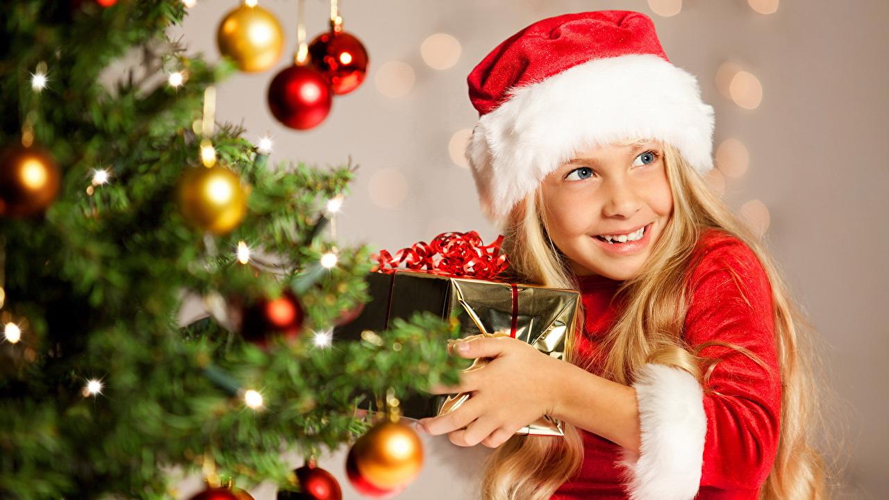 Фото Девочки Рождество Улыбка ребёнок шапка подарков Ветки Шарики Взгляд девочка Новый год улыбается Дети Шапки в шапке Подарки подарок Шар ветка ветвь на ветке смотрят смотрит