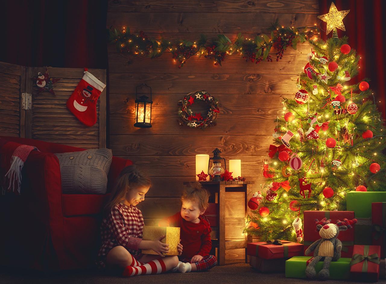 Фото девочка мальчик Рождество ребёнок Двое Новогодняя ёлка Подарки Свечи Шарики Гирлянда Девочки Мальчики мальчишка мальчишки Новый год Дети 2 два две Елка вдвоем подарок подарков Шар Электрическая гирлянда