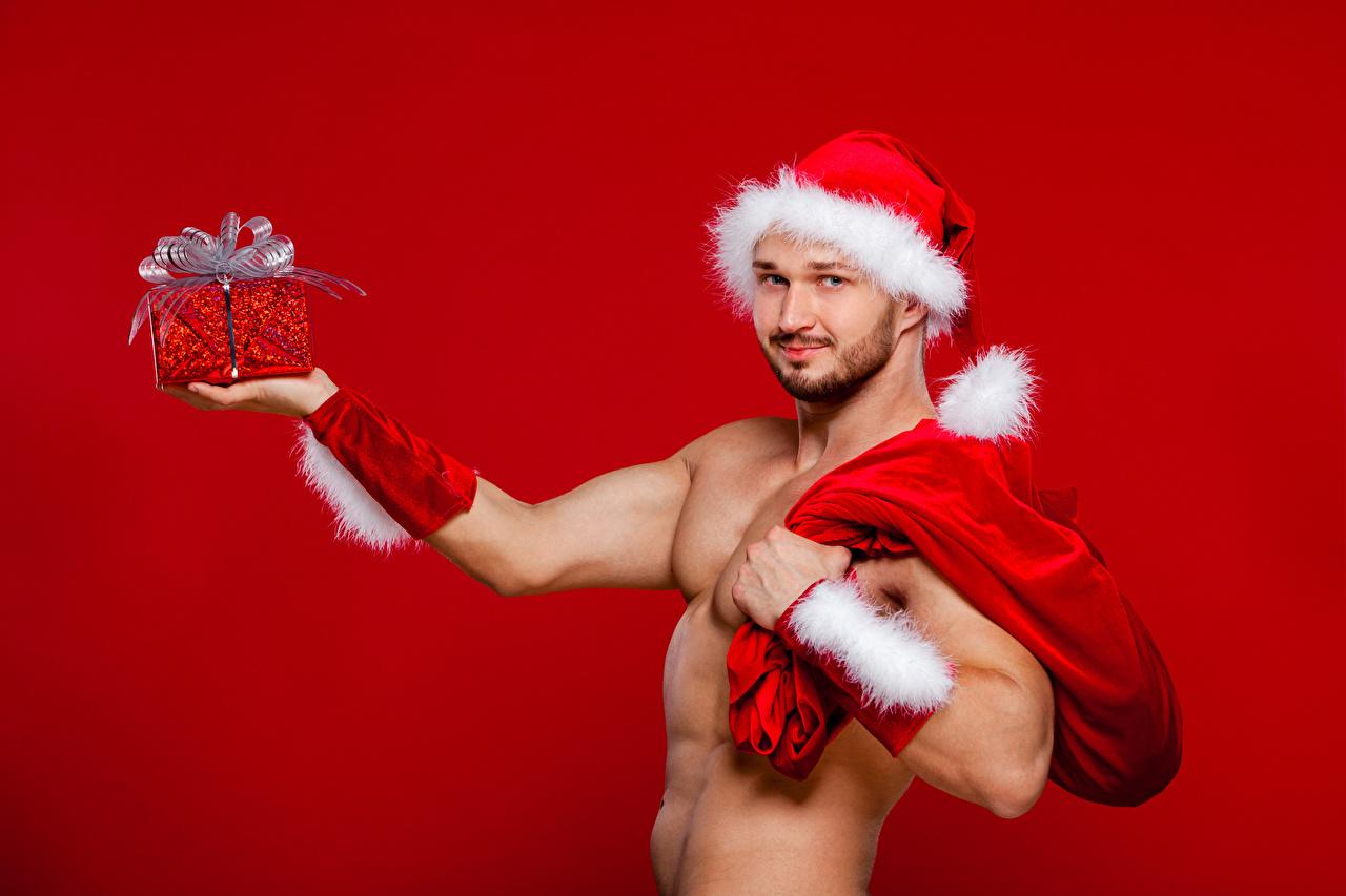 Фото Рождество Мужчины в шапке подарок Красный фон Новый год Шапки шапка Подарки подарков красном фоне