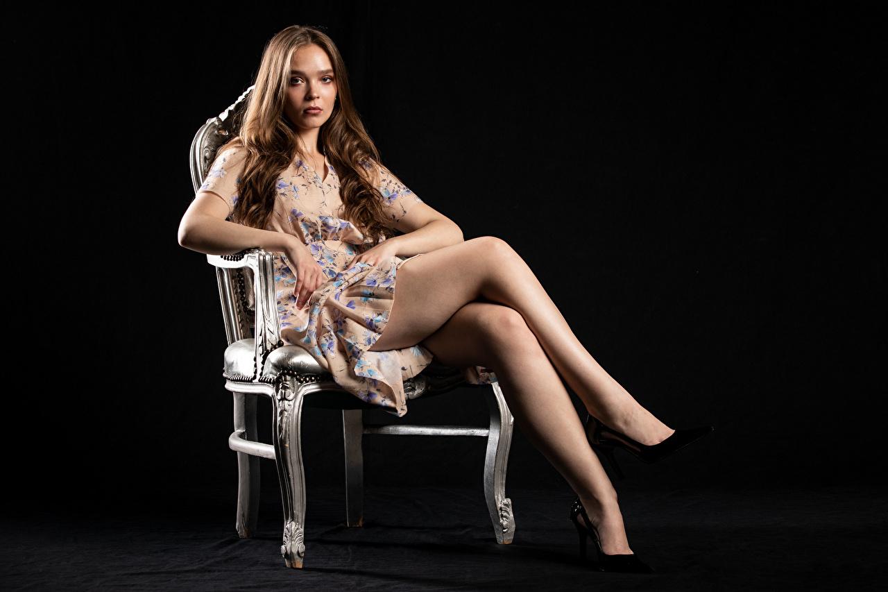 Фотография молодые женщины Silvy Sirius на черном фоне Сидит стул Модель Платье смотрят Ноги девушка Девушки молодая женщина Черный фон сидя сидящие Стулья фотомодель платья Взгляд смотрит ног