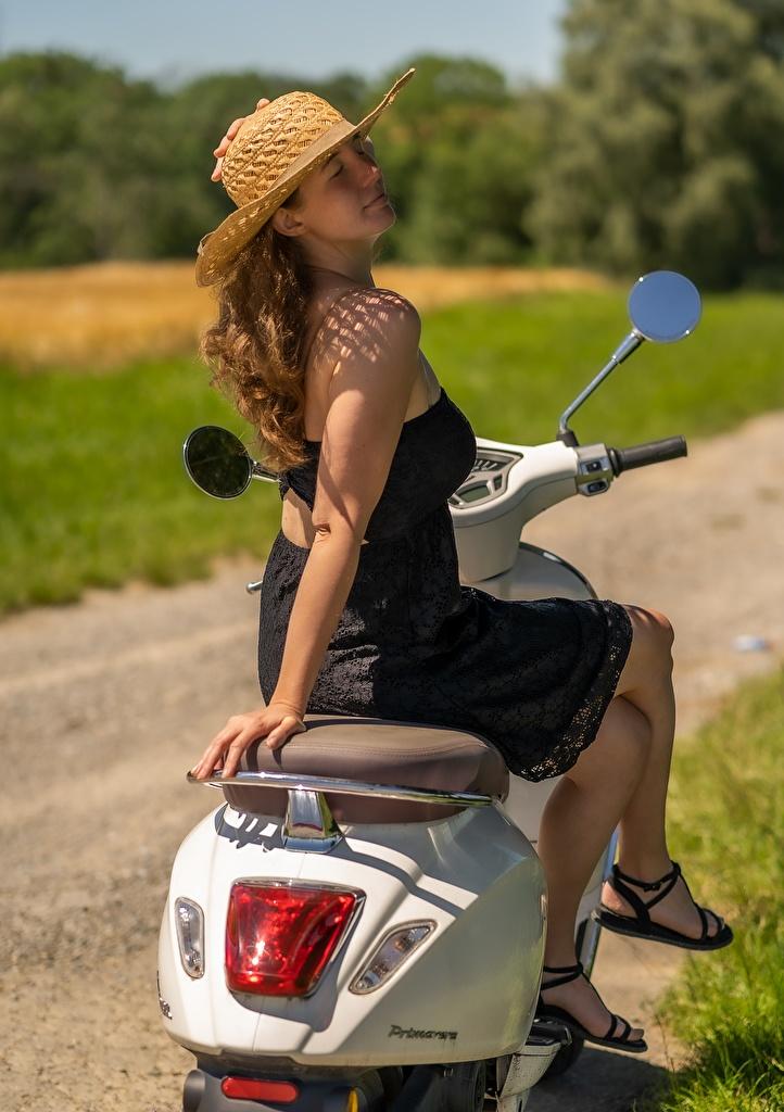 Картинка Скутер Шатенка Поза Шляпа молодые женщины ног Сидит платья  для мобильного телефона шатенки Мотороллер позирует шляпы шляпе девушка Девушки молодая женщина Ноги сидя сидящие Платье