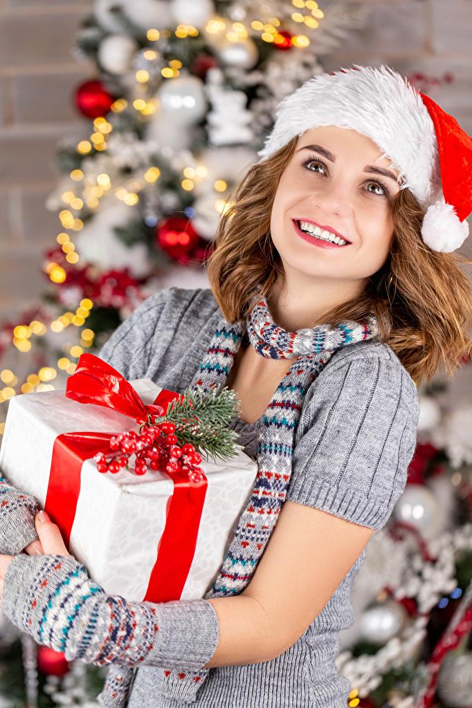 Фотографии Шатенка Новый год Улыбка шапка молодые женщины подарок Взгляд  для мобильного телефона шатенки Рождество улыбается Шапки в шапке девушка Девушки молодая женщина Подарки подарков смотрит смотрят