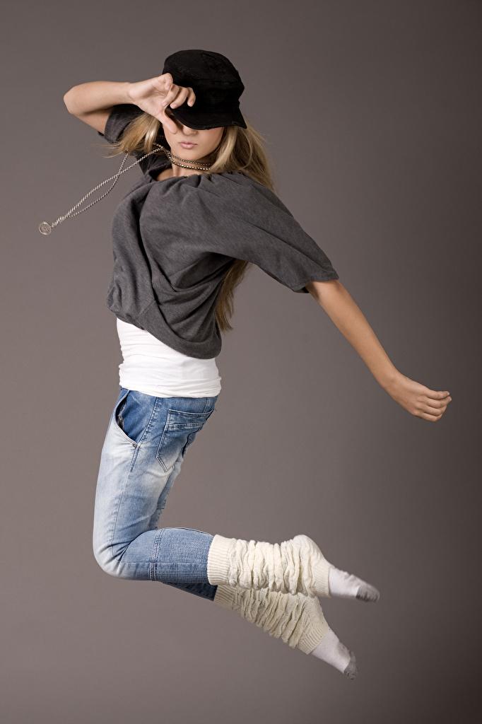 Фотографии Танцы Девушки Прыжок джинсов Руки Бейсболка сером фоне  для мобильного телефона танцует танцуют девушка молодая женщина молодые женщины Джинсы прыгает прыгать в прыжке рука Кепка кепке кепкой Серый фон
