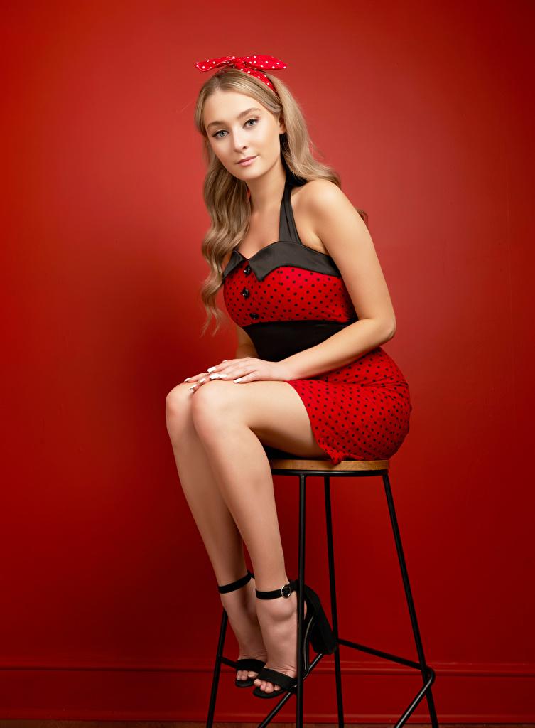 Фотографии Девушки Ноги стул бант сидящие смотрит красном фоне Платье  для мобильного телефона девушка молодая женщина молодые женщины ног сидя Сидит Стулья Бантик бантики Взгляд смотрят Красный фон платья