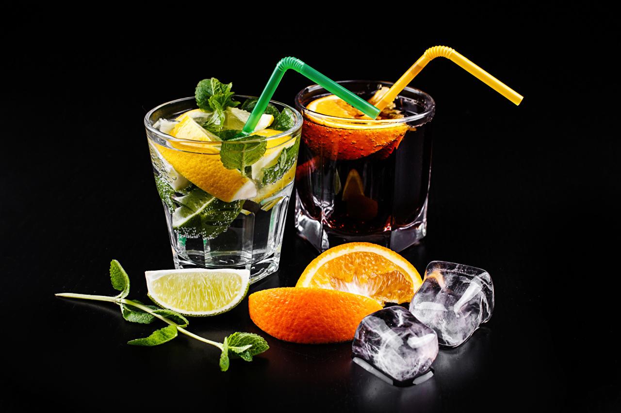Фотографии Алкогольные напитки Лед две Мохито Апельсин Стакан Лимоны Еда Коктейль на черном фоне льда 2 два Двое вдвоем стакана стакане Пища Продукты питания Черный фон