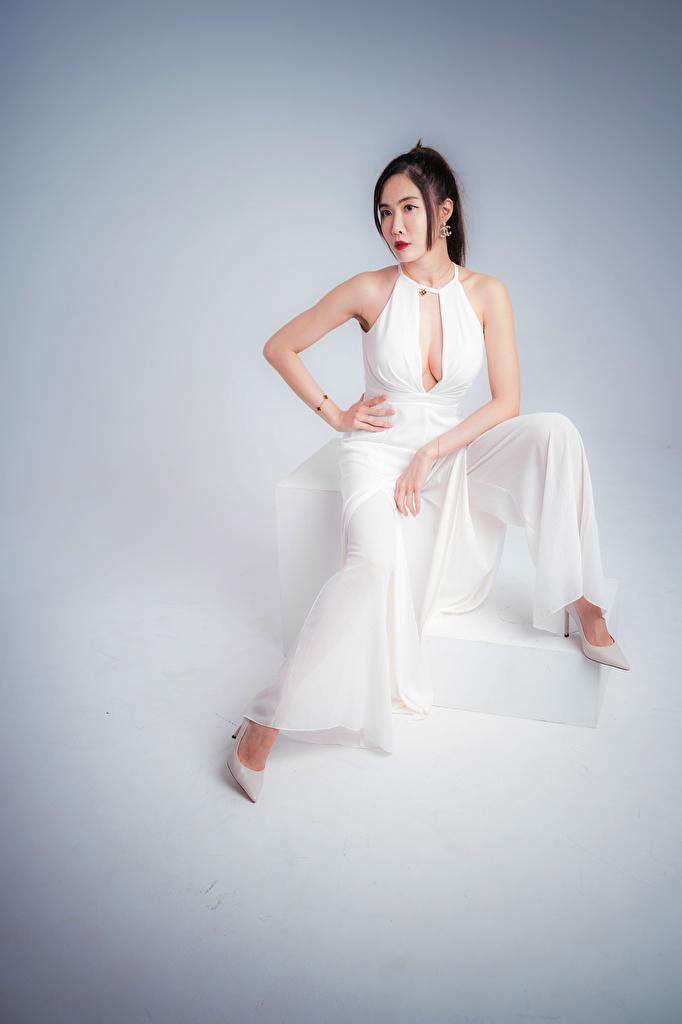 Фото позирует девушка азиатки Сидит сером фоне платья туфель  для мобильного телефона Поза Девушки молодая женщина молодые женщины Азиаты азиатка сидя сидящие Серый фон Платье Туфли туфлях