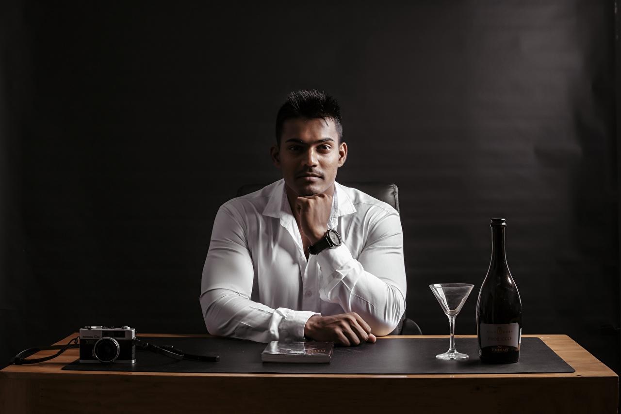 Фотография Индийские мужчина Фотоаппарат рубашки рука Бокалы сидящие бутылки Взгляд Мужчины фотокамера Рубашка рубашке Руки сидя Сидит бокал Бутылка смотрят смотрит