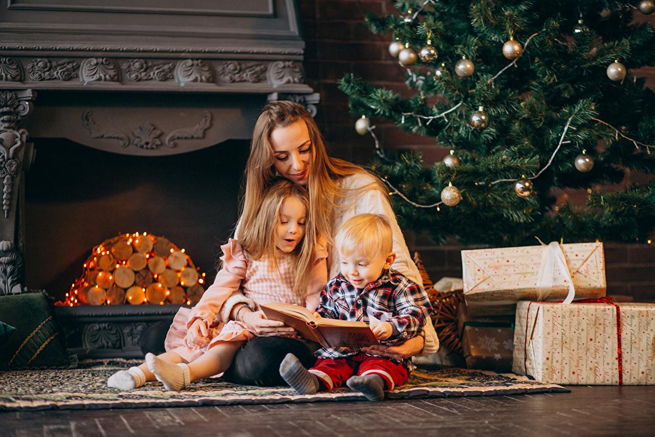 Обои для рабочего стола Девочки Мальчики Новый год Мать ребёнок подарок Сидит книги втроем девочка мальчик мальчишка мальчишки Рождество Мама Дети Подарки подарков три сидя Трое 3 Книга сидящие