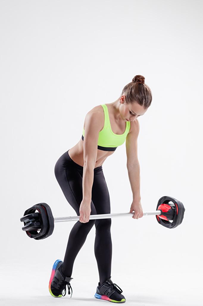 Картинки Шатенка Физические упражнения Фитнес Спорт Штанга Девушки Серый фон Тренировка