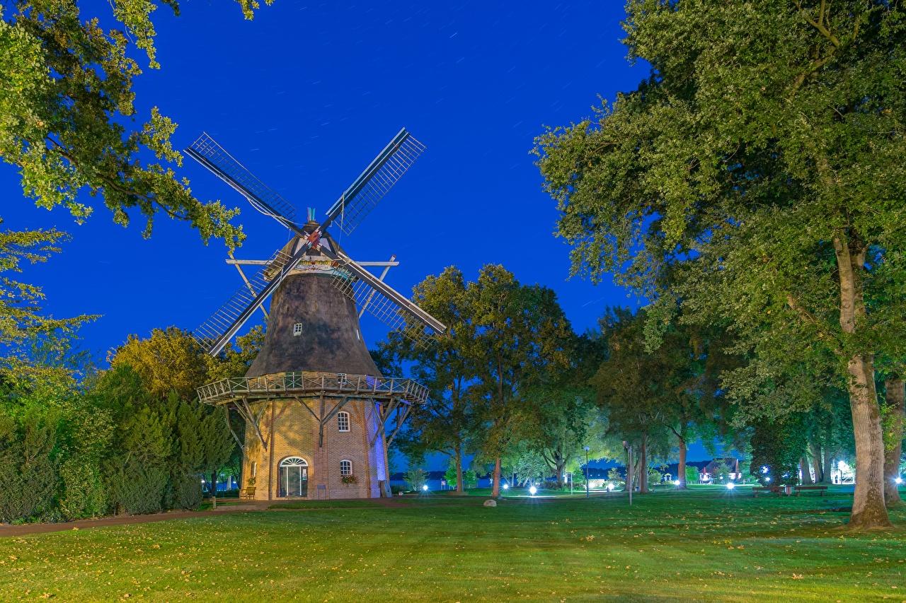 Картинка Германия ветряная мельница Bad Zwischenahnн, Lower Saxony Трава в ночи город дерева мельницы Мельница Ночь ночью траве Ночные дерево Города Деревья деревьев