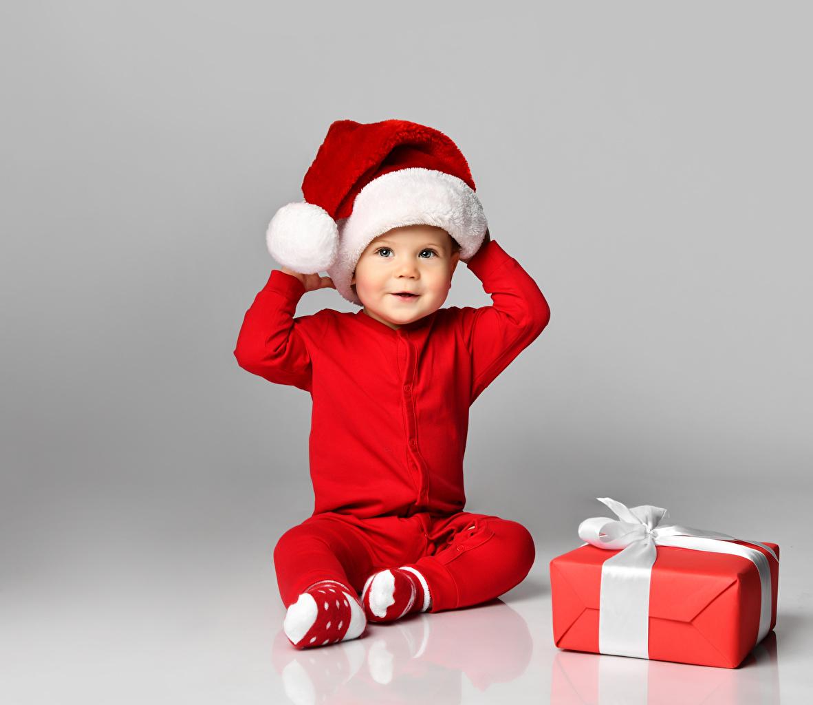 Картинка мальчишка Новый год Дети Шапки Подарки Сидит Униформа смотрит Серый фон мальчик Мальчики мальчишки Рождество ребёнок шапка в шапке подарок подарков сидя сидящие униформе Взгляд смотрят сером фоне