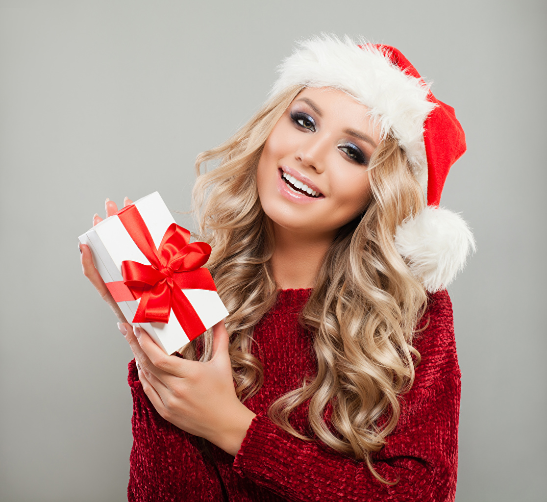 Картинки девушка Серый фон Рождество Шапки Руки Волосы Блондинка улыбается подарков Кудрявые Девушки молодые женщины молодая женщина Новый год сером фоне шапка в шапке рука волос блондинок блондинки Улыбка Подарки подарок кудри