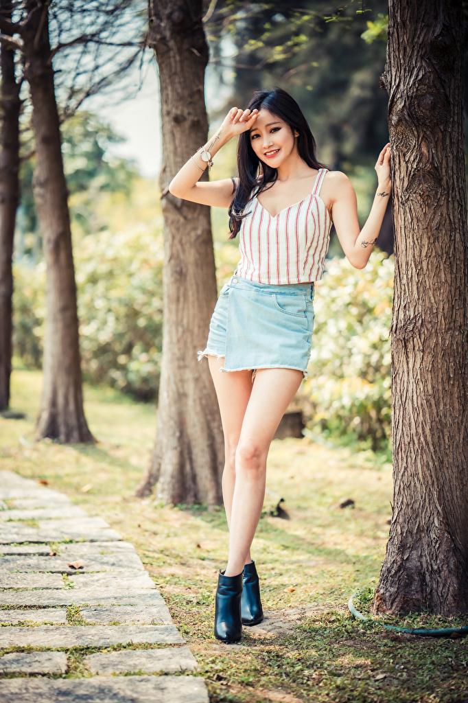 Фотографии юбки улыбается позирует Девушки ног Майка азиатки Ствол дерева  для мобильного телефона Юбка юбке Улыбка Поза девушка молодая женщина молодые женщины Ноги майки майке Азиаты азиатка