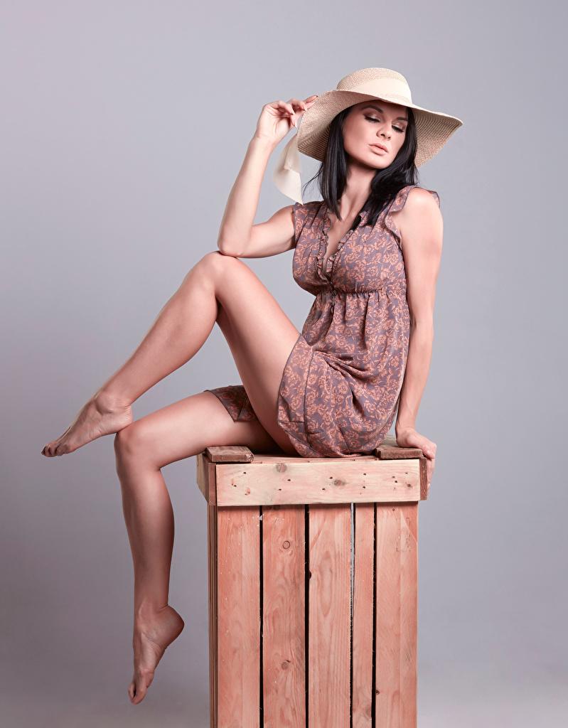 Фотографии Брюнетка Поза красивый Шляпа Девушки Ноги сидящие платья  для мобильного телефона брюнетки брюнеток красивая Красивые позирует шляпы шляпе девушка молодая женщина молодые женщины ног сидя Сидит Платье
