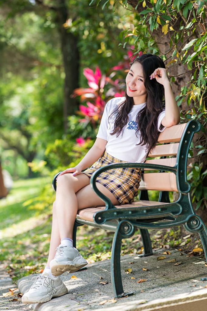 Картинка юбки Размытый фон Футболка молодые женщины Ноги азиатки Сидит Скамейка  для мобильного телефона Юбка юбке боке девушка Девушки футболке молодая женщина ног Азиаты азиатка сидя Скамья сидящие