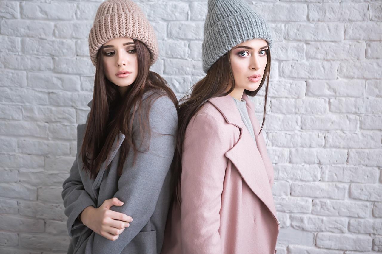 Обои для рабочего стола Пальто две Шапки девушка из кирпича Стена смотрит 2 два Двое шапка вдвоем в шапке Девушки молодая женщина молодые женщины Кирпичный стене стены стенка Взгляд смотрят