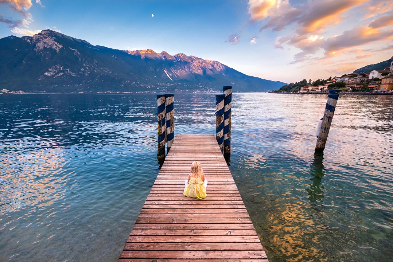Обои для рабочего стола девочка Италия Limone sul Garda Lombardy Дети гора Природа Озеро Пирсы сидящие Девочки ребёнок Горы сидя Сидит Причалы Пристань