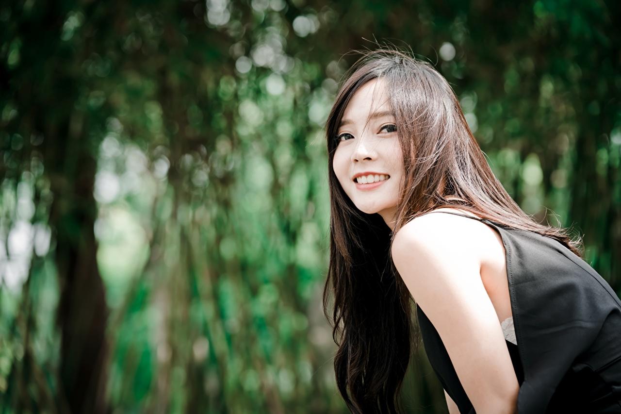 Фото Шатенка Улыбка боке молодая женщина азиатка Взгляд шатенки улыбается Размытый фон девушка Девушки молодые женщины Азиаты азиатки смотрит смотрят