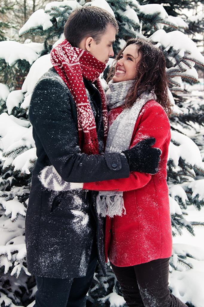 Картинки Шарф Мужчины любовники Улыбка Пальто две зимние Объятие молодые женщины Снег  для мобильного телефона шарфе шарфом мужчина Влюбленные пары улыбается 2 два Зима Двое вдвоем Девушки девушка обнимает обнимаются молодая женщина снеге снегу снега