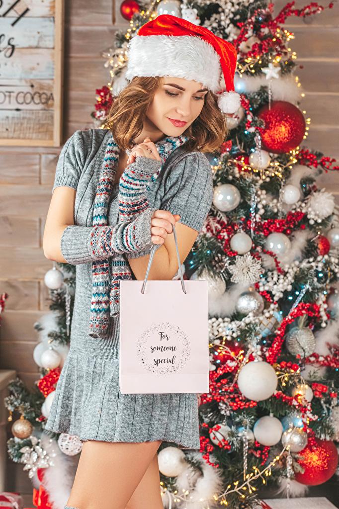 Фотография Шатенка Рождество Елка шапка молодые женщины подарков Шарики платья  для мобильного телефона шатенки Новый год Шапки в шапке девушка Девушки Новогодняя ёлка молодая женщина подарок Подарки Шар Платье