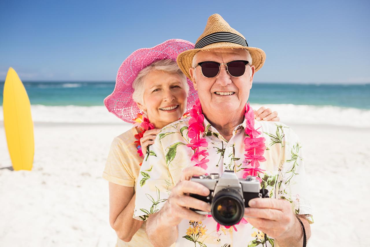 Фото путешественник мужчина Старуха фотокамера Улыбка Старик два шляпы очков Турист Мужчины Фотоаппарат старая женщина пожилая женщина улыбается старый мужчина пожилой мужчина 2 две Двое Шляпа шляпе вдвоем Очки очках