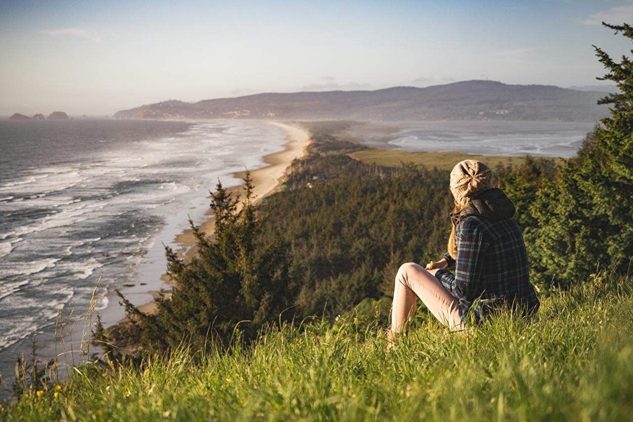 Фотографии Море шапка Природа молодые женщины берег Трава сидящие Шапки в шапке Девушки девушка молодая женщина сидя Сидит траве Побережье
