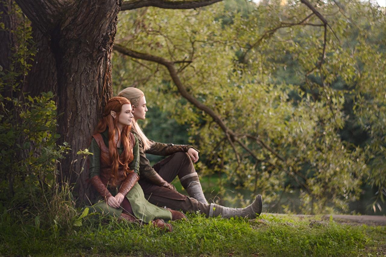 Фотографии Хоббит Эльфы Мужчины Косплей Парни Legolas Tauriel LuckyStrikeCosplay Девушки Ствол дерева траве сидящие юноша парень подросток сидя Трава Сидит