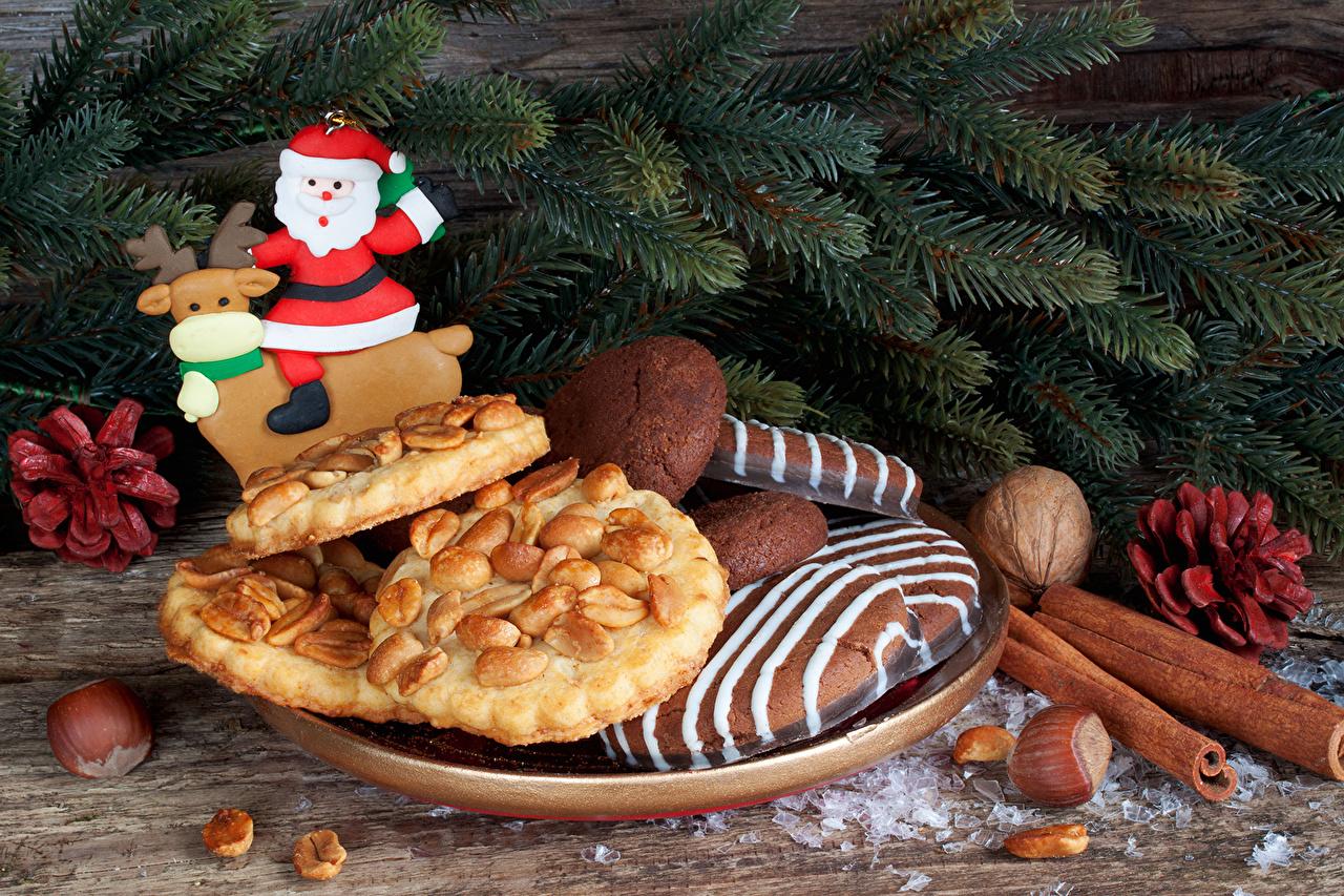 Картинки Новый год Дед Мороз Корица Еда ветвь Печенье Орехи Выпечка Рождество Санта-Клаус Пища Ветки ветка на ветке Продукты питания