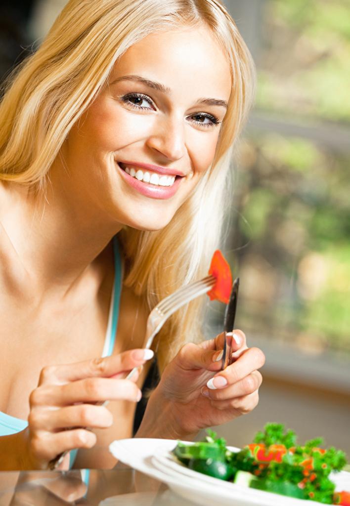 Картинка Блондинка Улыбка Девушки Пальцы Вилка столовая смотрят  для мобильного телефона блондинки блондинок улыбается девушка молодая женщина молодые женщины вилки Взгляд смотрит