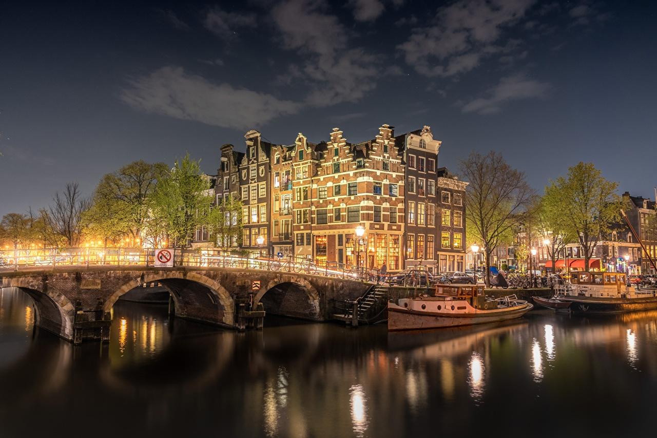 Фотографии Амстердам Нидерланды Мосты Водный канал Речные суда Реки ночью Города Здания голландия мост Ночь река речка в ночи Ночные Дома город