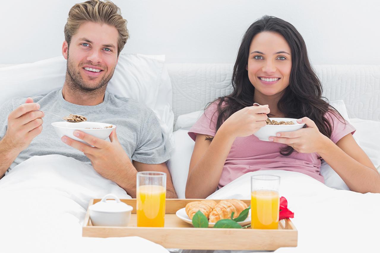 Фотографии Брюнетка Мужчины Улыбка Сок Двое Девушки Завтрак Стакан Взгляд 2 вдвоем смотрит