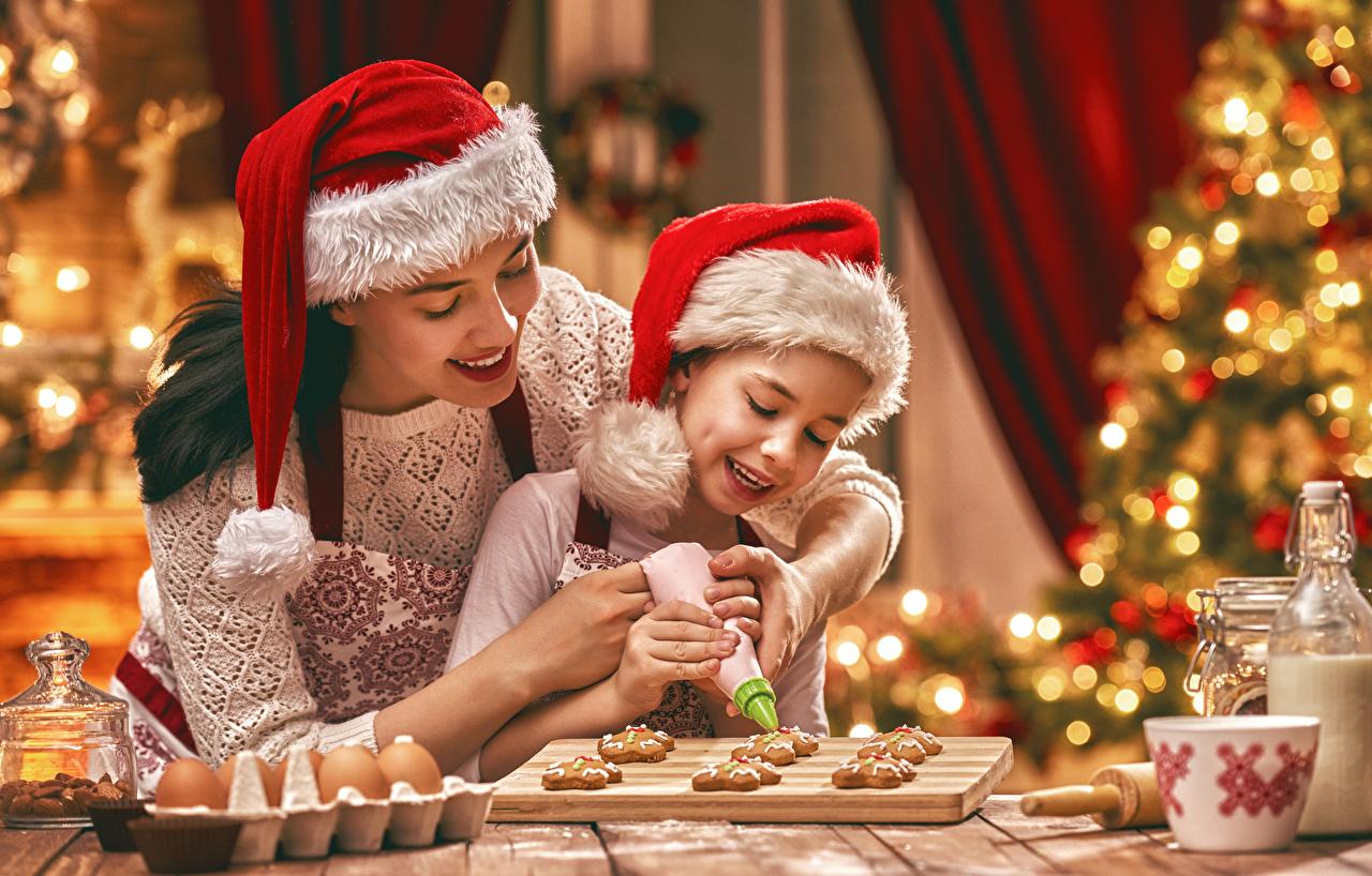 Фотография Девочки Рождество Улыбка Мать Дети 2 Шапки Девушки Печенье девочка Новый год улыбается Мама ребёнок две два Двое шапка вдвоем в шапке девушка молодые женщины молодая женщина