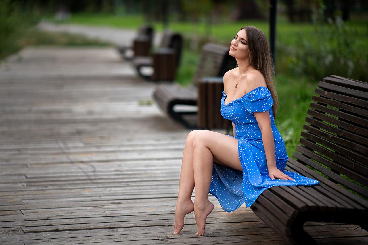 Картинки Модель улыбается Размытый фон Девушки Ноги Скамья сидящие Платье фотомодель Улыбка боке девушка молодая женщина молодые женщины ног сидя Сидит Скамейка платья