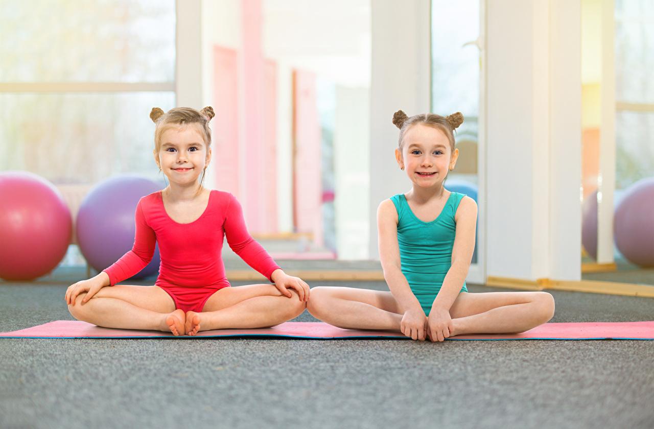 Фотографии Девочки Дети Двое Гимнастика сидящие Униформа Взгляд Ребёнок 2 вдвоем Сидит смотрит
