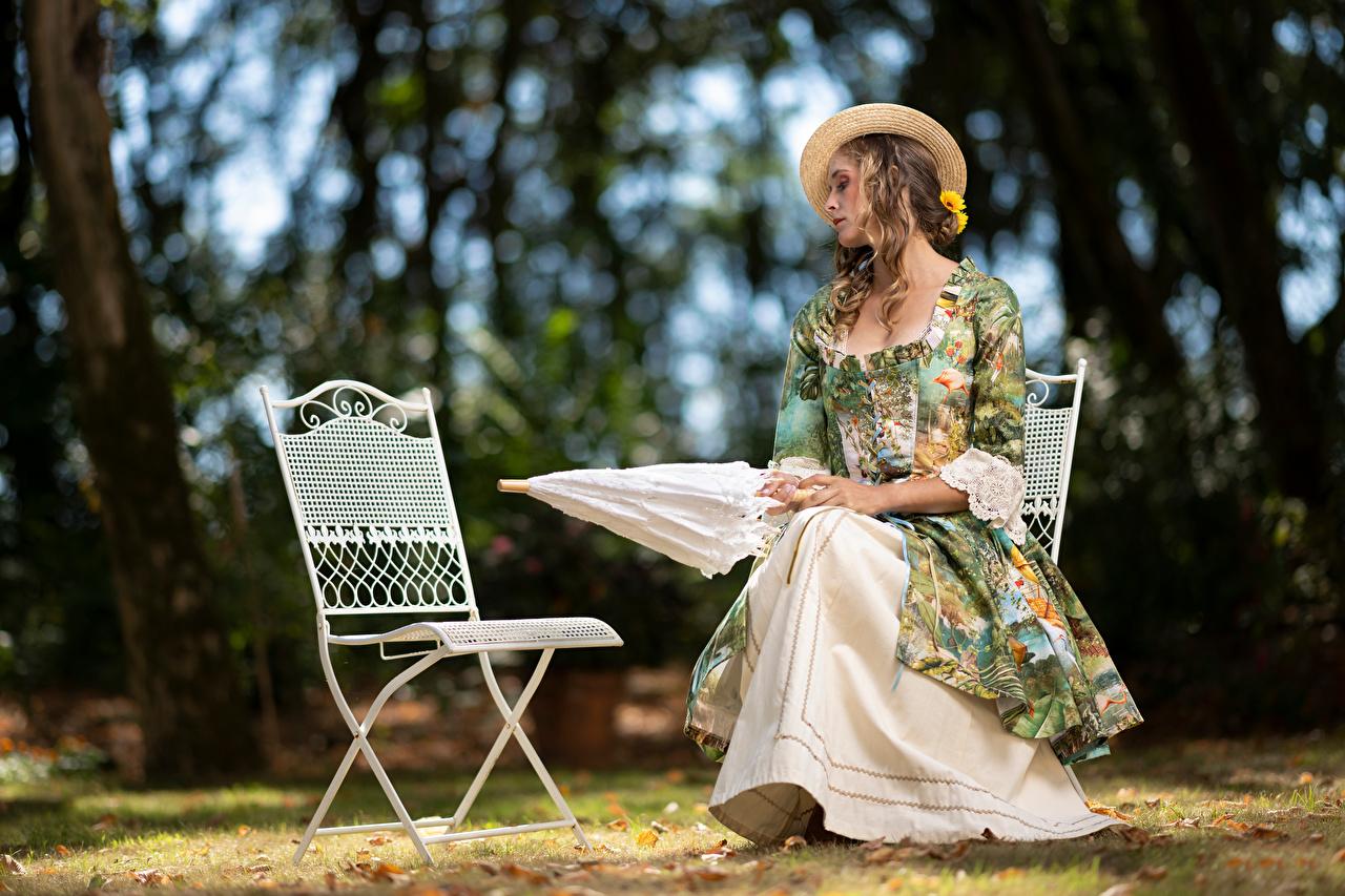 Картинка Размытый фон Шляпа Девушки сидя Стулья зонтом Платье боке шляпы шляпе девушка молодая женщина молодые женщины стул Зонт Сидит зонтик сидящие платья