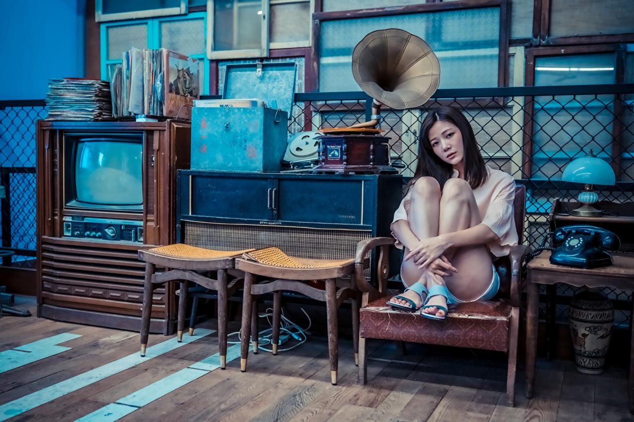 Фотография Грампластинка Телефон молодая женщина Ноги азиатка ТВ ламп Сидит Кресло смотрит грампластинки девушка Девушки телефона телефоном молодые женщины ног Азиаты азиатки сидя Лампа лампы сидящие Телевизор Взгляд смотрят