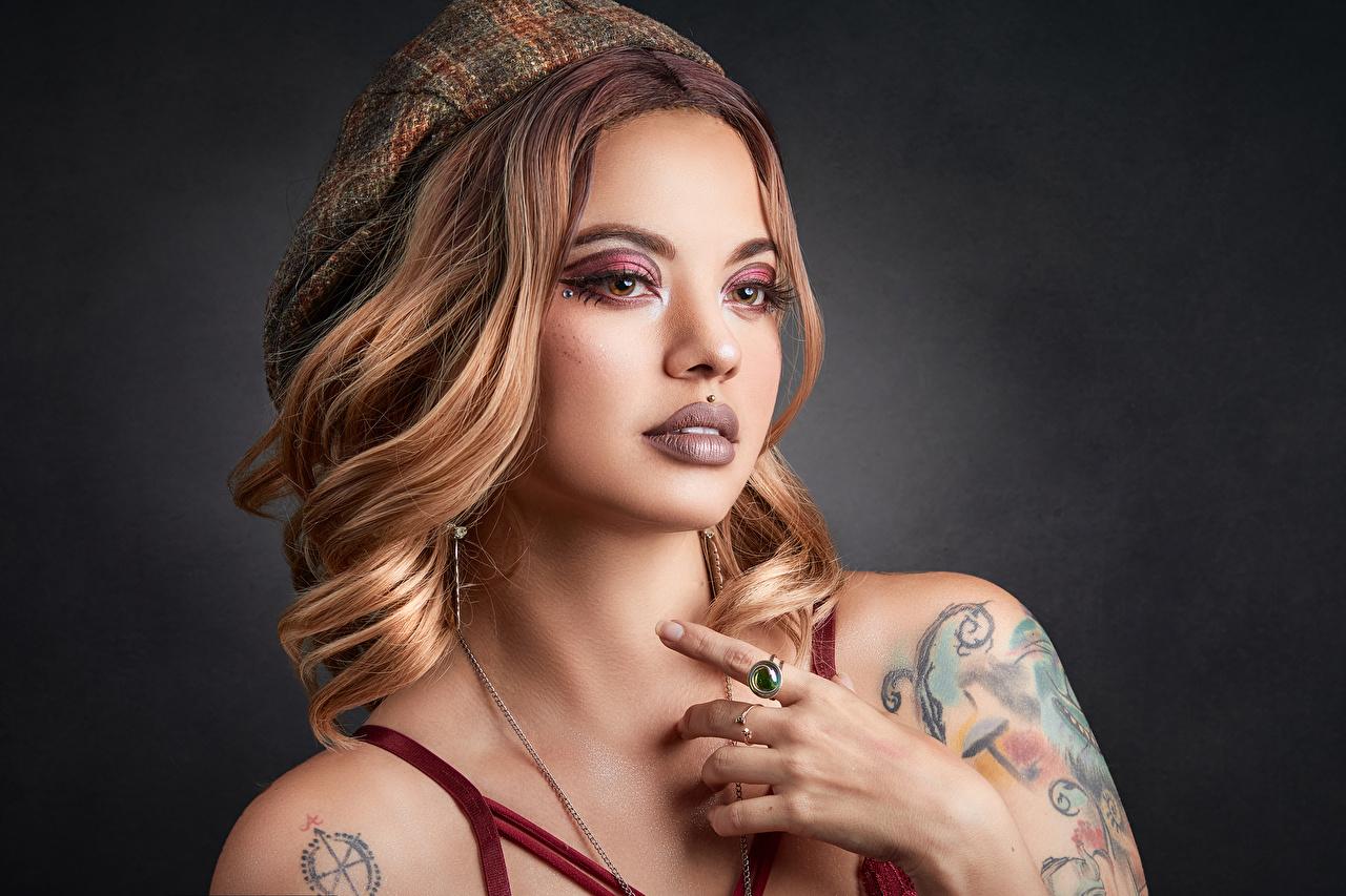 Фотография Татуировки пирсингом косметика на лице Берет молодая женщина Руки смотрит тату татуировка Пирсинг мейкап Макияж девушка Девушки молодые женщины рука Взгляд смотрят