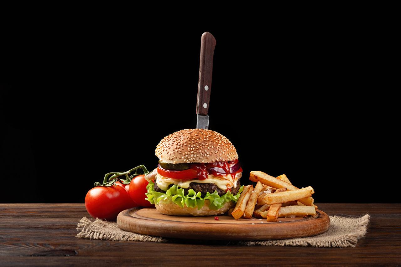 Фотография Нож Томаты Гамбургер Картофель фри Продукты питания разделочной доске Черный фон ножик Помидоры Еда Пища Разделочная доска на черном фоне