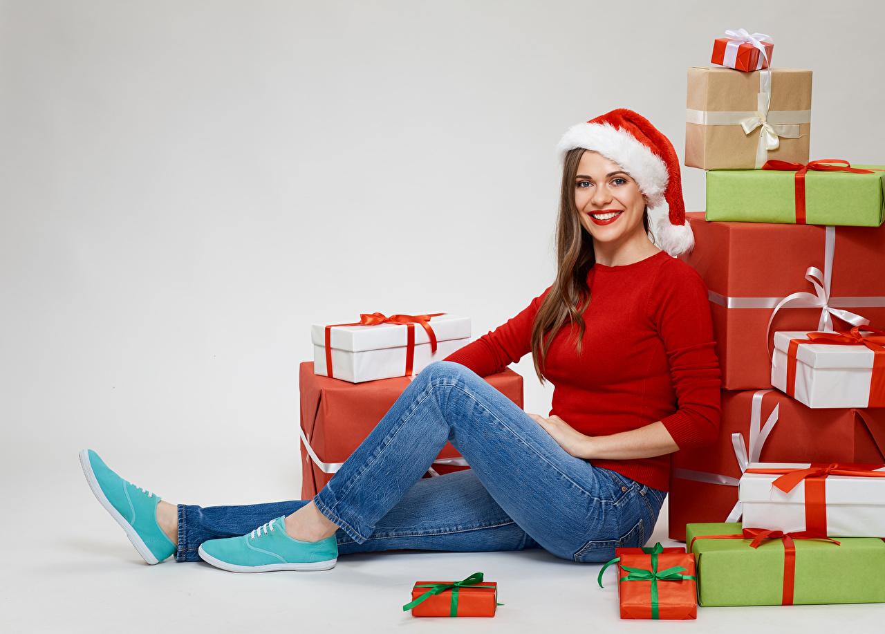Обои Шатенка Новый год Улыбка Шапки Девушки Джинсы Подарки Сидит смотрит Серый фон Рождество сидящие Взгляд