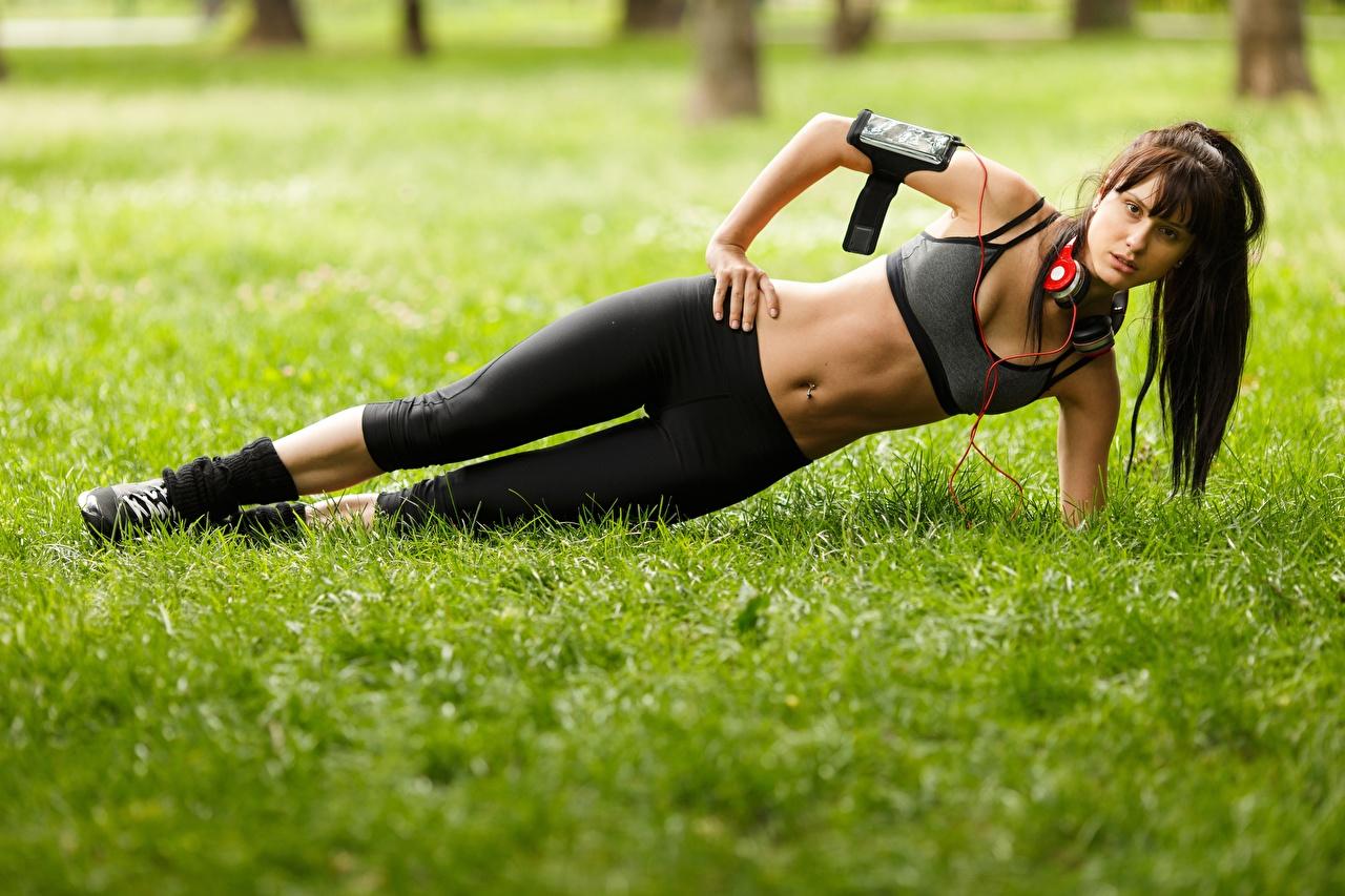 Фото Шатенка в наушниках физическое упражнение Фитнес молодые женщины Живот Трава шатенки Наушники Тренировка тренируется девушка Девушки молодая женщина траве живота