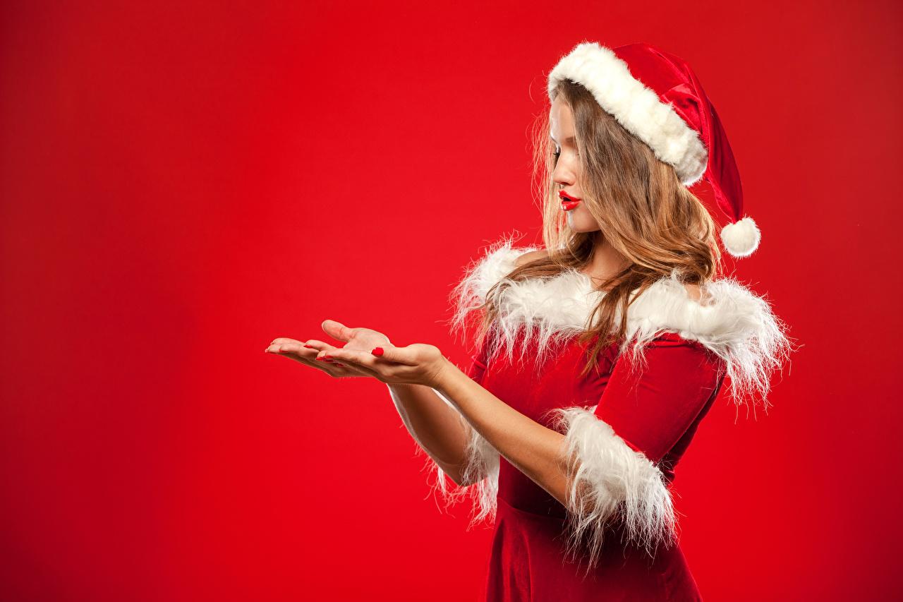 Фотография Новый год Шапки Девушки рука униформе Красный фон Рождество шапка в шапке девушка молодые женщины молодая женщина Руки Униформа красном фоне