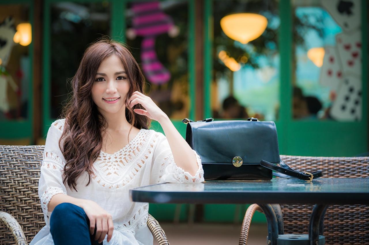 Фотографии Шатенка Улыбка боке молодые женщины Азиаты Руки Сидит Сумка Взгляд шатенки улыбается Размытый фон девушка Девушки молодая женщина азиатка азиатки рука сидя сидящие смотрят смотрит