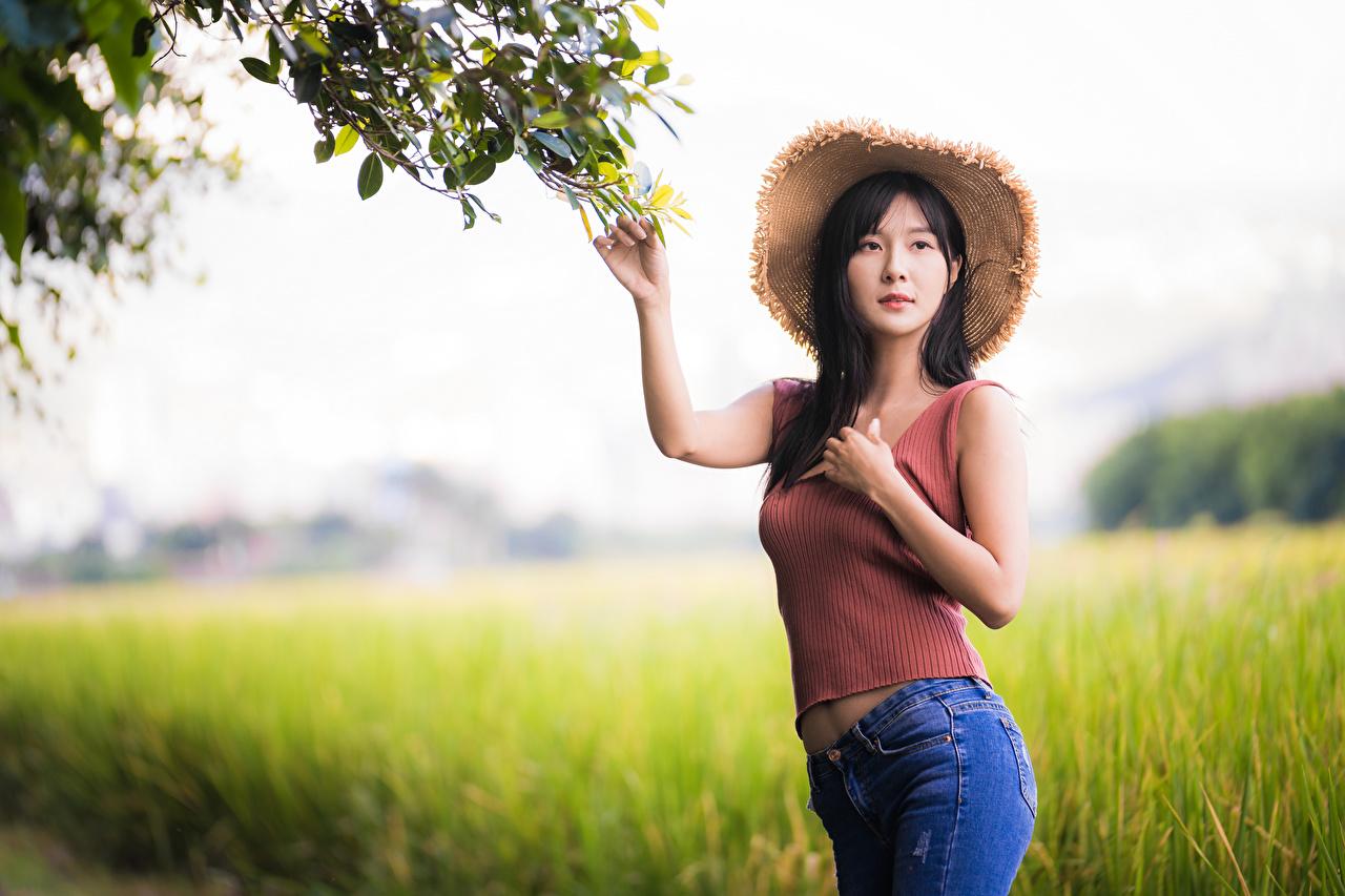 Фото боке позирует шляпы девушка майки Джинсы азиатка смотрят Размытый фон Поза Шляпа шляпе Девушки молодая женщина молодые женщины Майка майке Азиаты азиатки джинсов Взгляд смотрит
