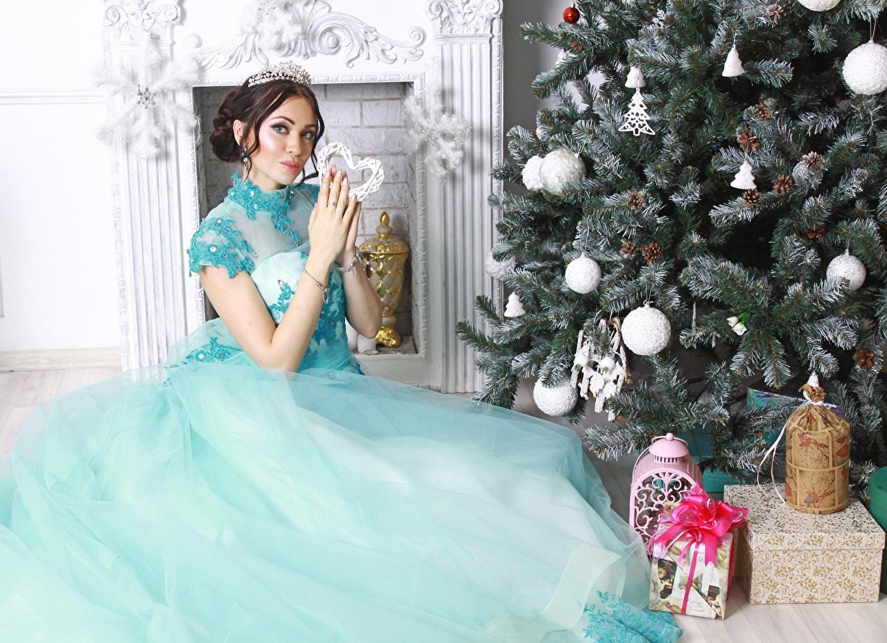 Картинка Шатенка Рождество Елка Девушки Подарки Сидит Платье Новый год Новогодняя ёлка сидящие