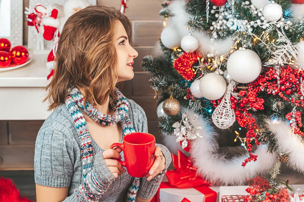 Картинки Шатенка Рождество Елка девушка Шарики Кружка шатенки Новый год Девушки Новогодняя ёлка молодая женщина молодые женщины Шар кружки кружке