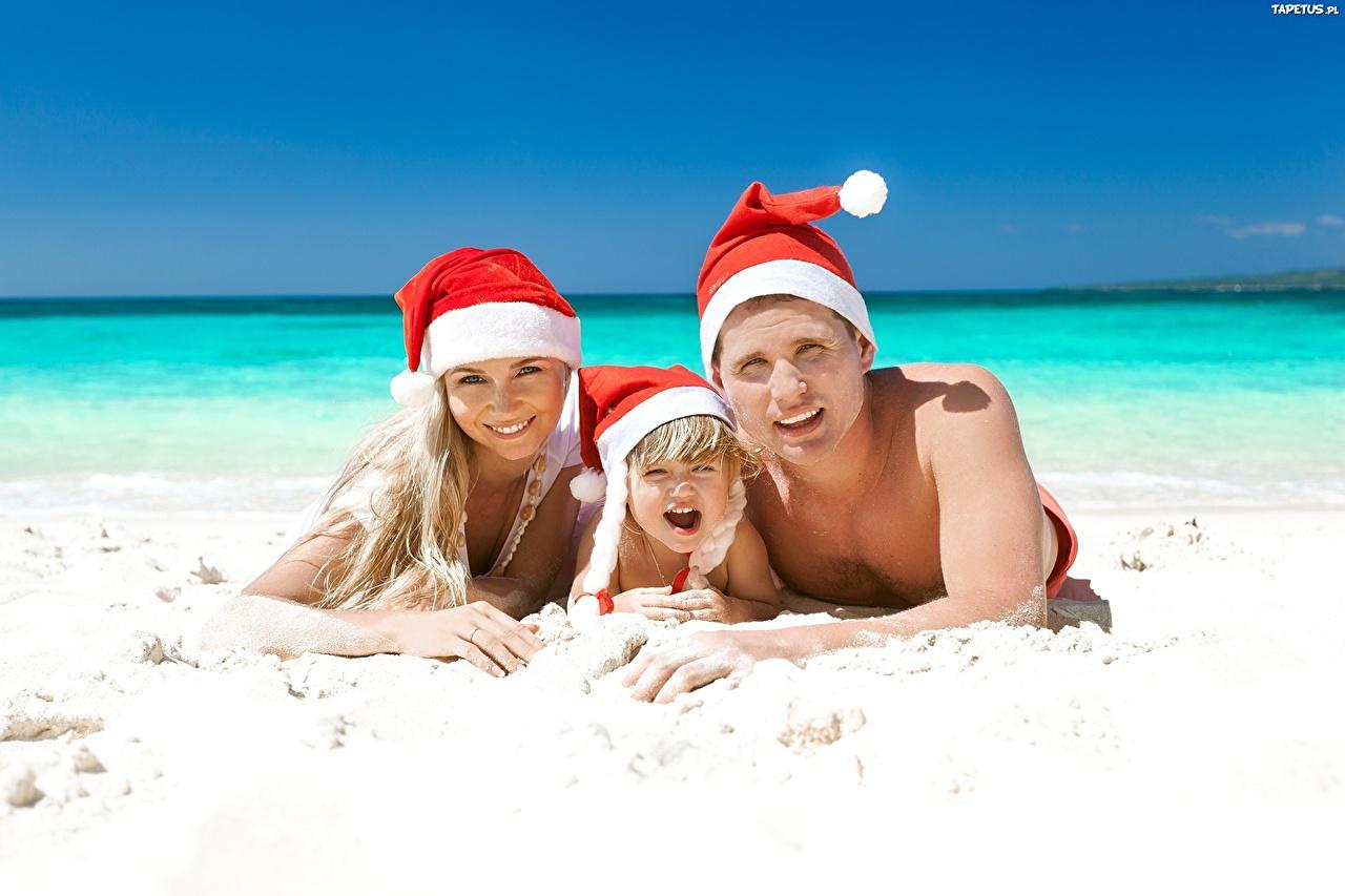 Фотографии Новый год Мужчины Пляж Ребёнок Море Шапки Девушки Песок Трое 3 Рождество Дети втроем