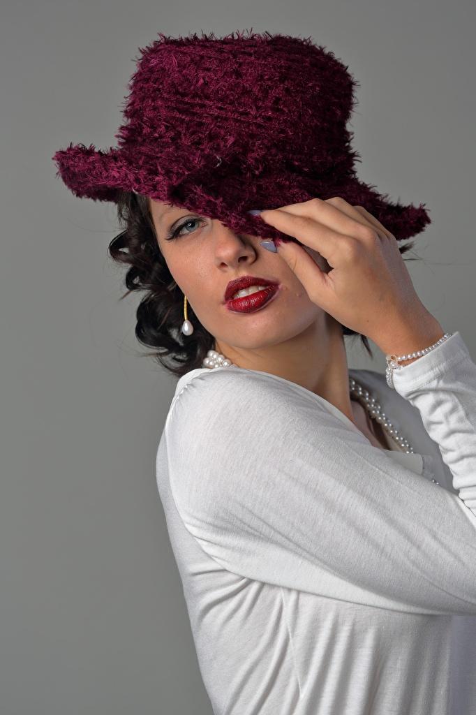 Фото брюнеток мейкап позирует шляпе Девушки Руки Взгляд Серый фон  для мобильного телефона брюнетки Брюнетка Макияж косметика на лице Поза шляпы Шляпа девушка молодая женщина молодые женщины рука смотрят смотрит сером фоне